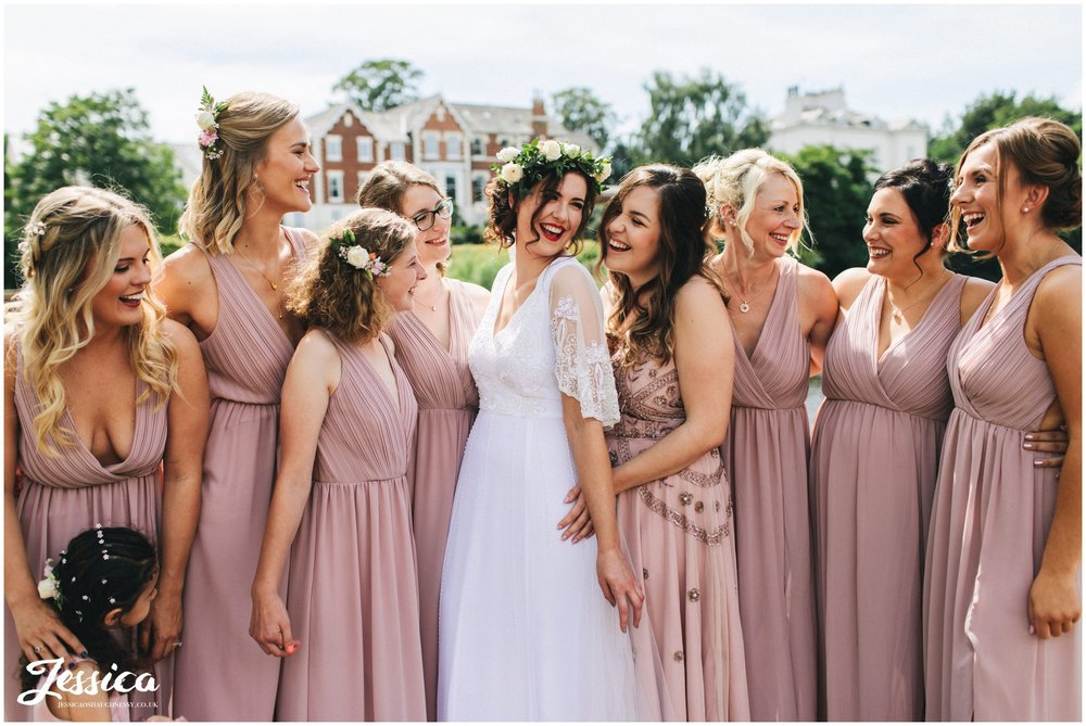 bride poses in front of the river dee with her bridesmaids