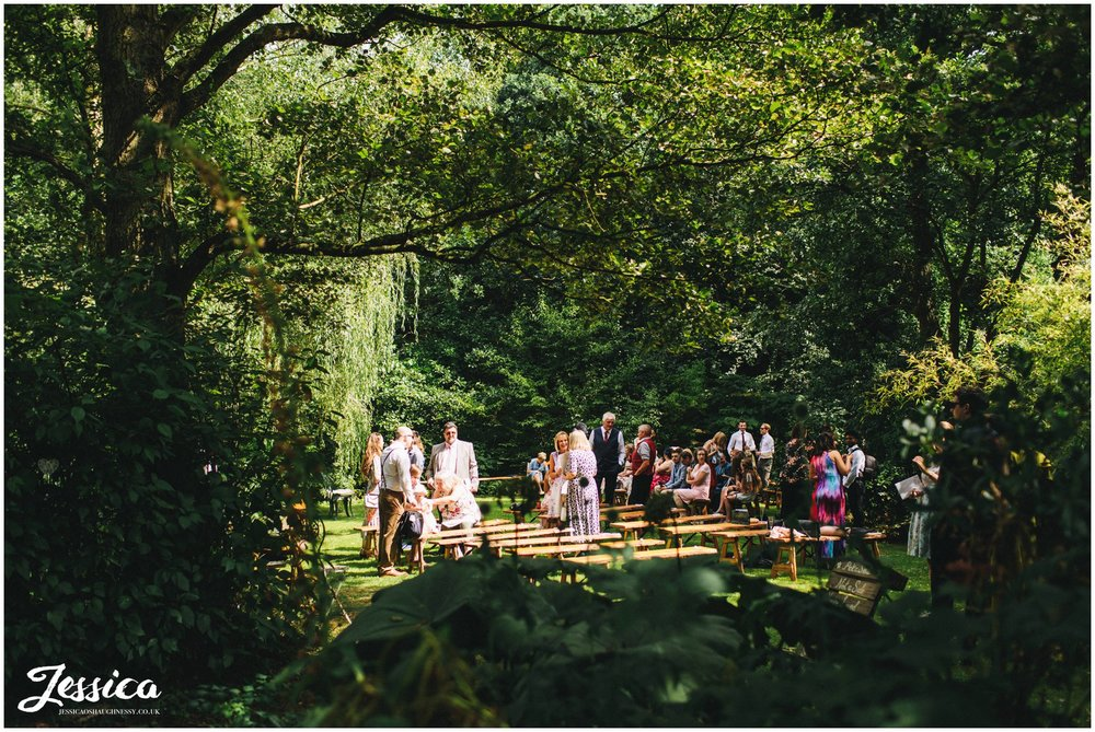guests take their seats for an outdoor ceremony at stonyford cottage gardens