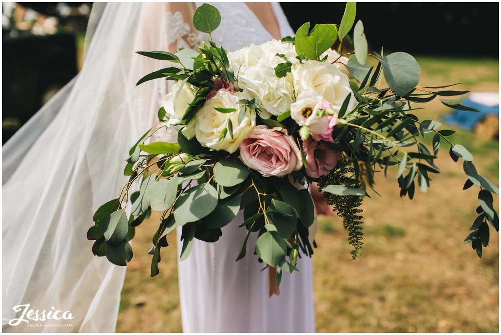 the bride holds her boho bouquet