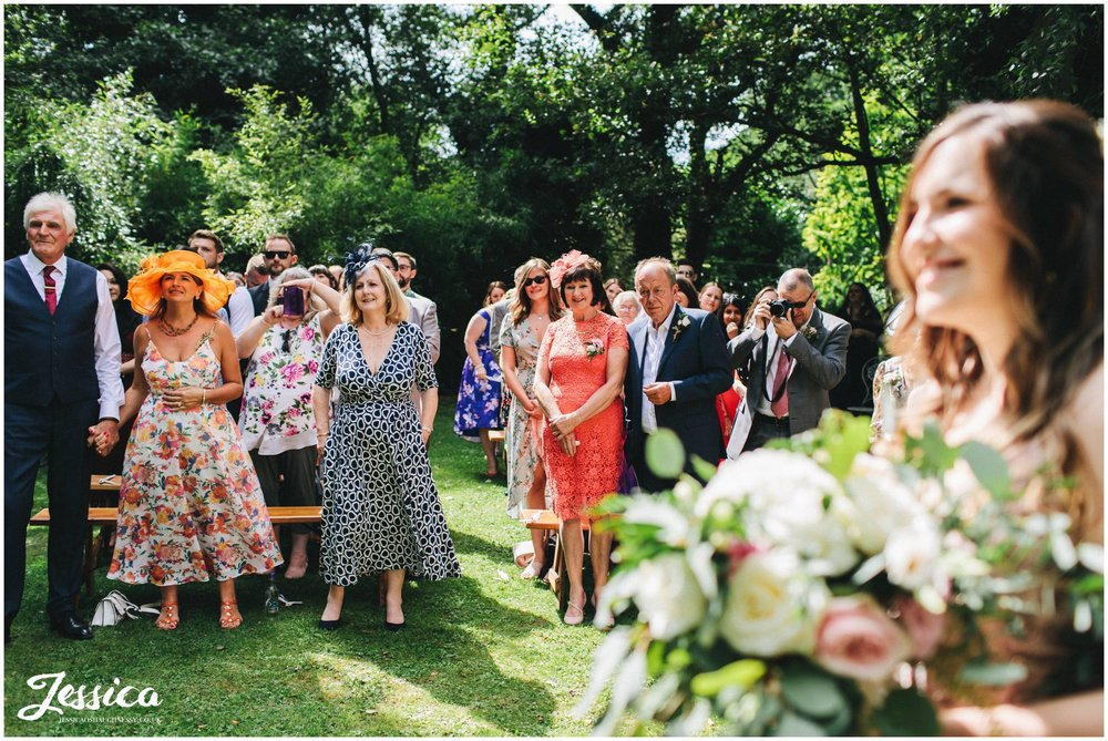 wedding guests smile during the outdoor ceremony