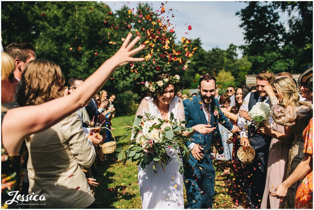 the couple run through their confetti line in the sun
