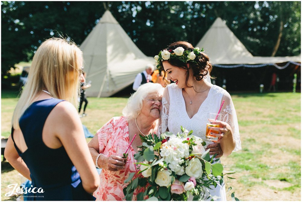 the bride hugs her grandma at the tipi wedding