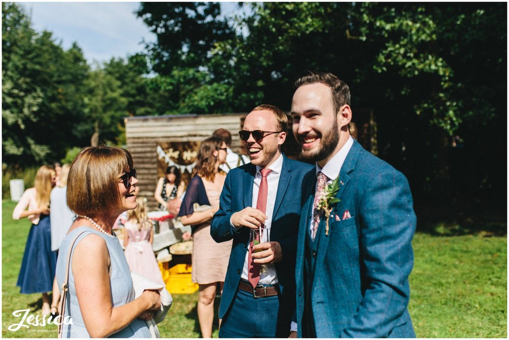 groom laughs with his friends in the sunshine