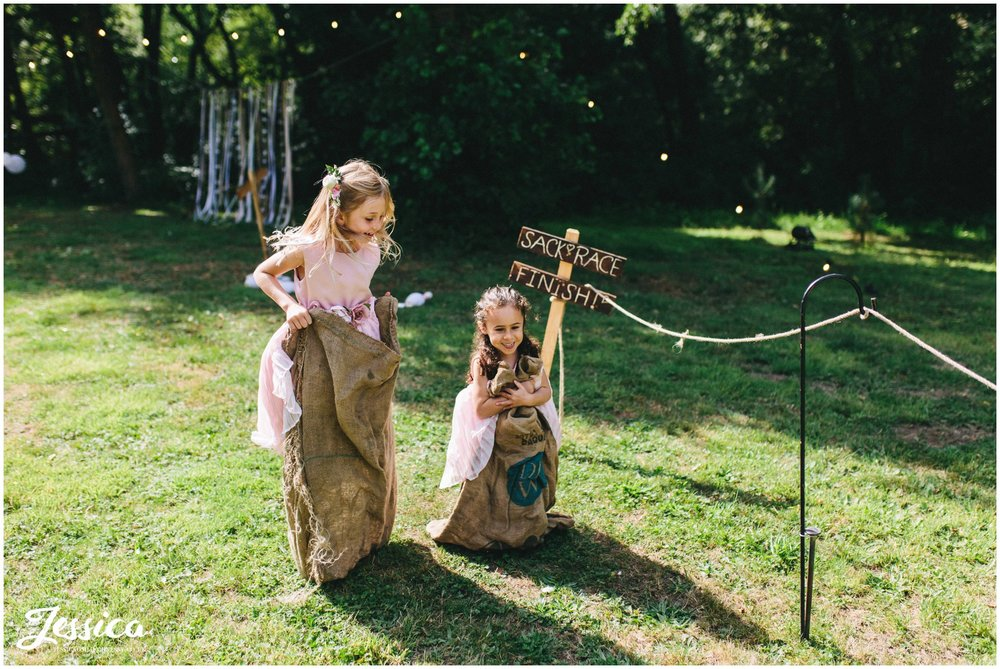 flower girls play in hessian sacks