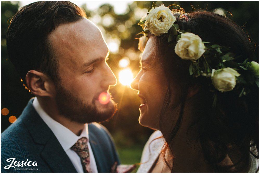 couple kiss as the sun sets during their boho tipi wedding