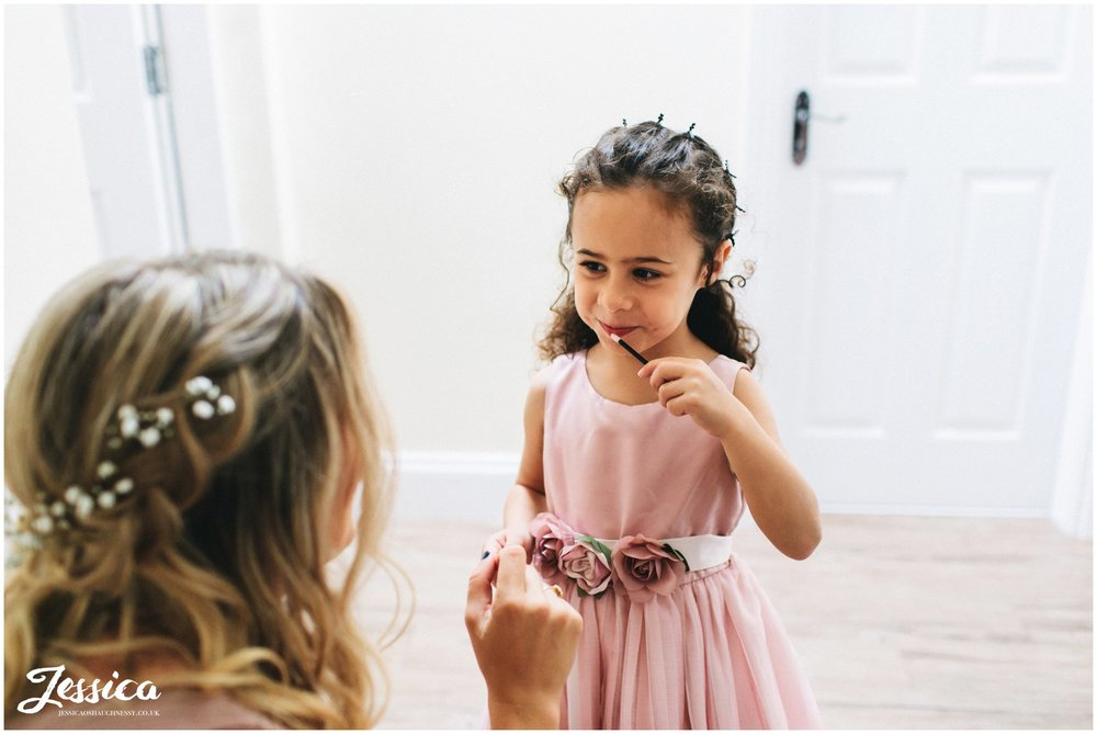 flower girl puts on lip gloss