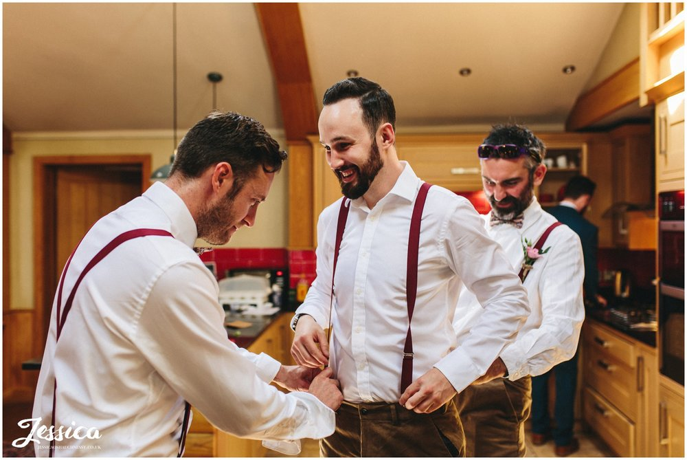 groomsmen help dress the best man