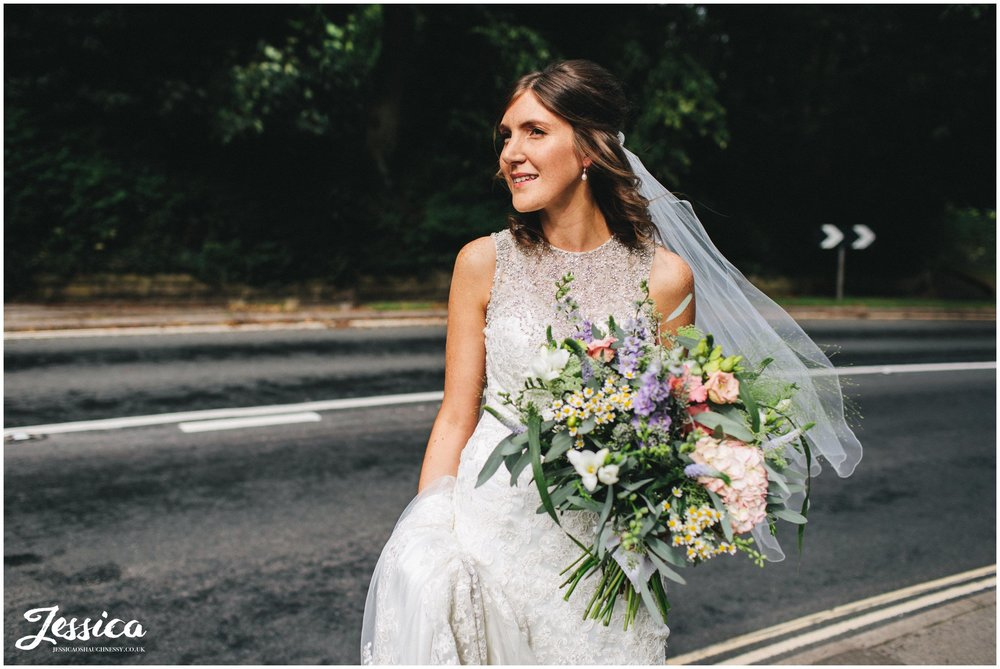 Bride waits at the road side for her bridal party to catch up