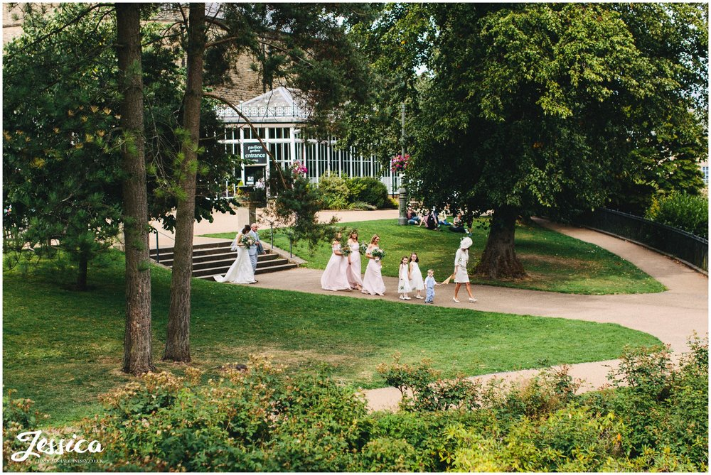 Bride & bridesmaids walk through the gardens to the band stand