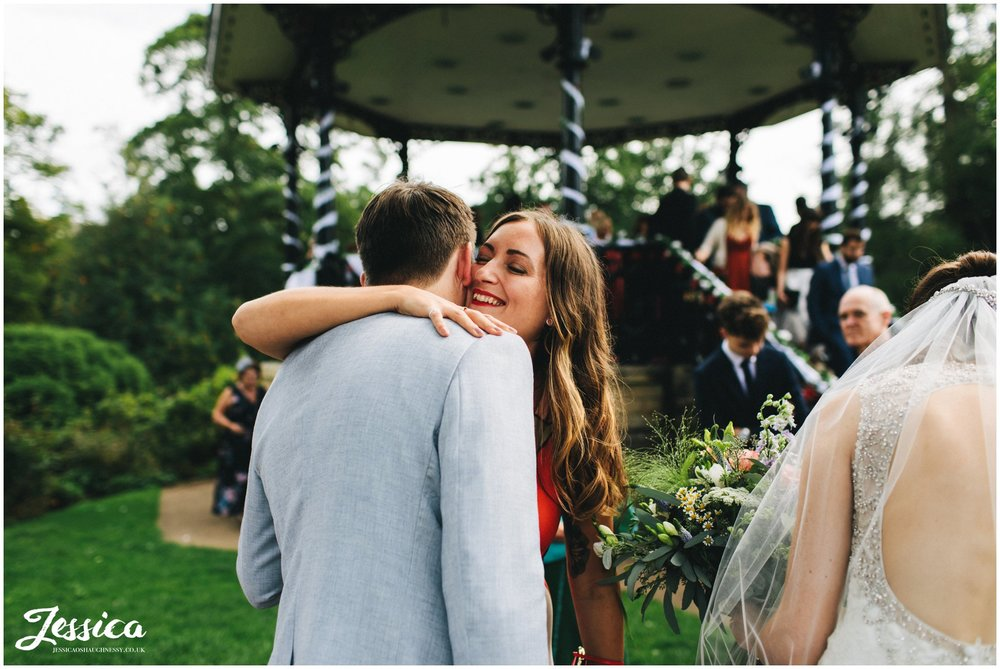 groom hugs his sister after his outdoor wedding ceremony