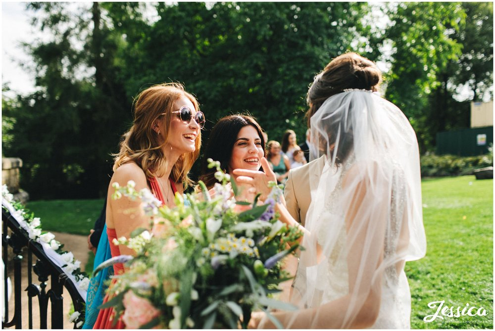 brides friends admire her in her wedding dress