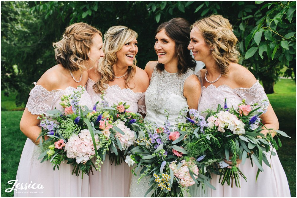 bride and bridesmaids laugh together for their group photograph