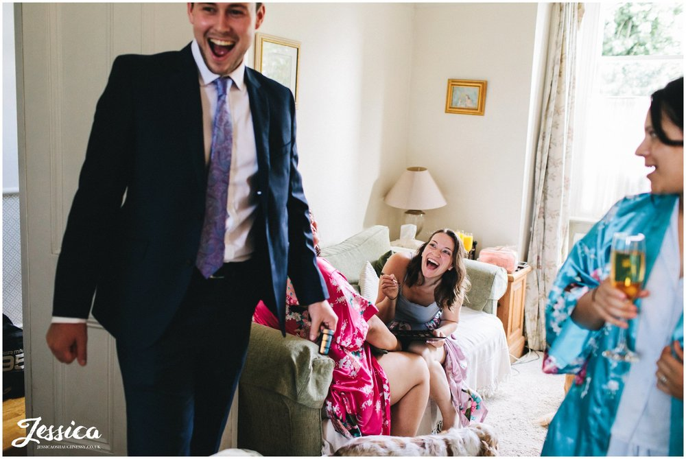 bridesmaids laughing whilst preparing for the wedding