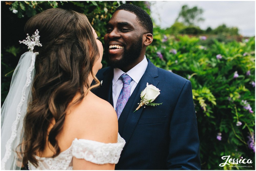the groom laughs as he speaks to his new wife