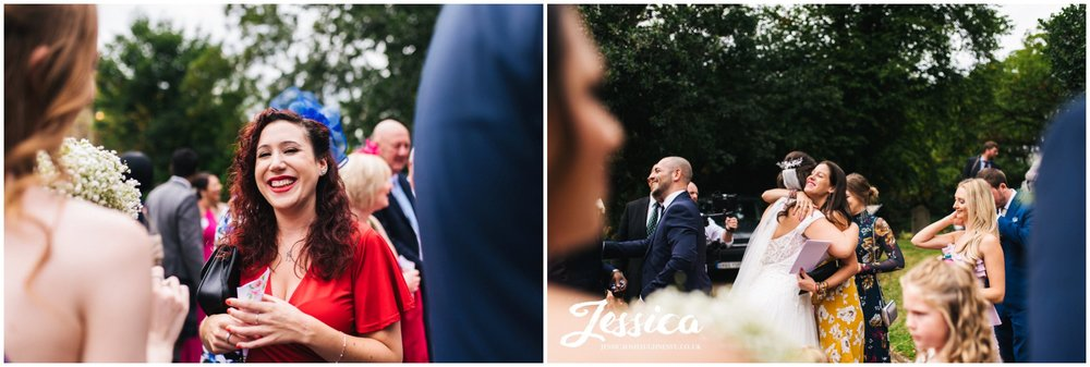 wedding guests laugh outside the church