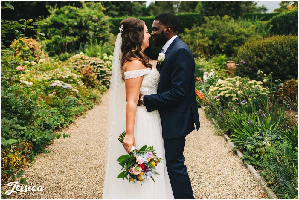 the bride and groom kiss in gaynes park gardens