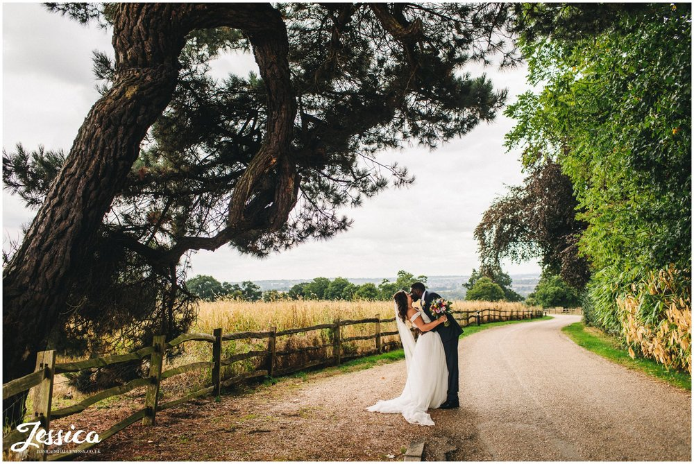 husband and wife kiss under a huge tree on gaynes park driveway