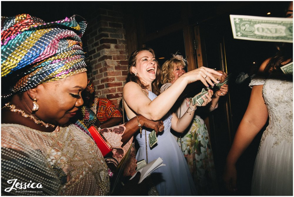 wedding guests throw dollars over the new couple
