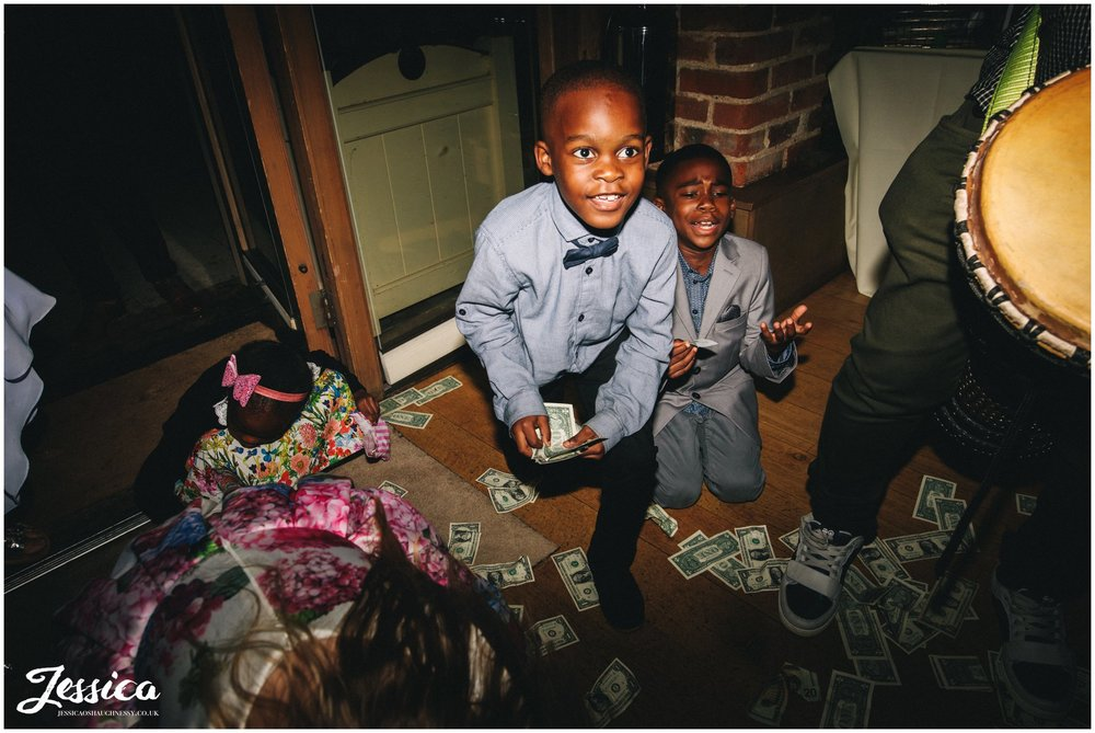 children pick up the fallen money
