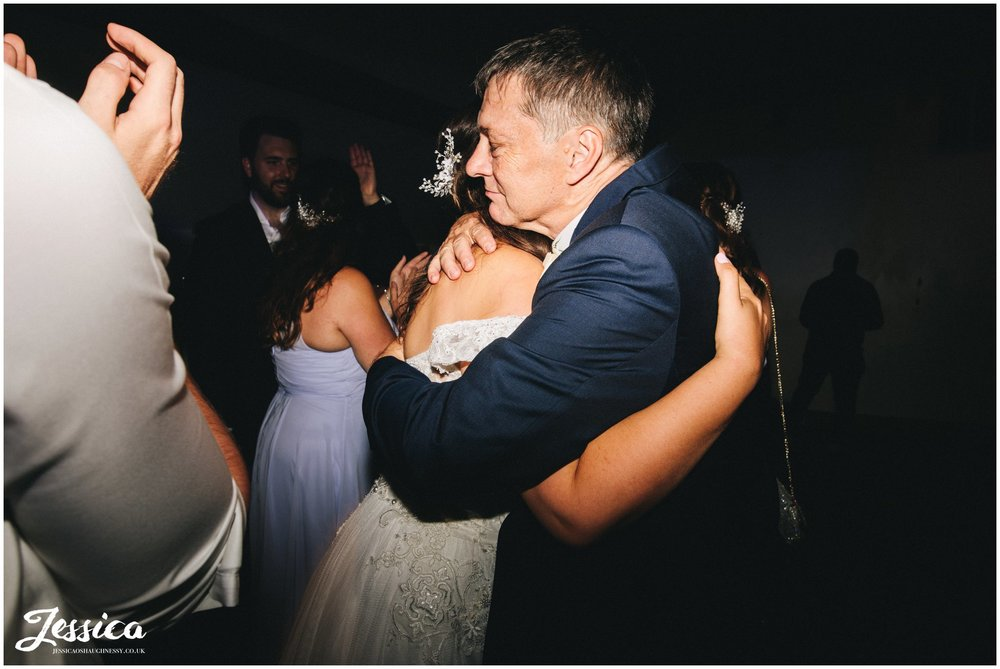 the bride hugs her father on the dancefloor at gaynes park