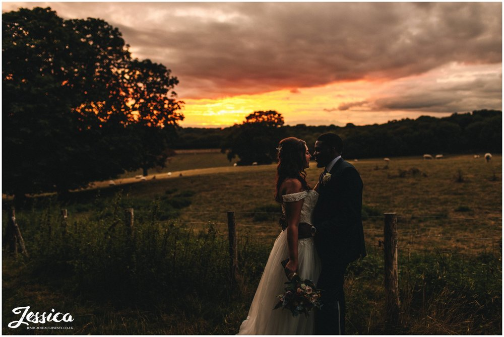 the couple stand in front of the sunset at gaynes park in epping