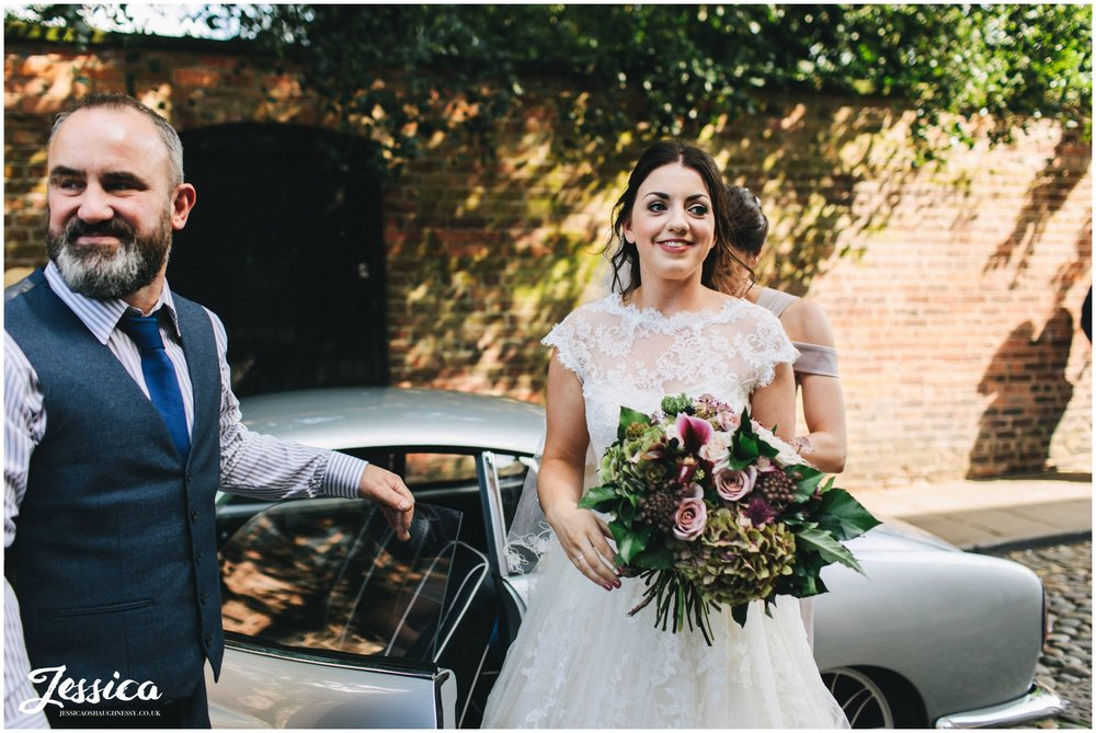 bride gets out of the car and heads to the church