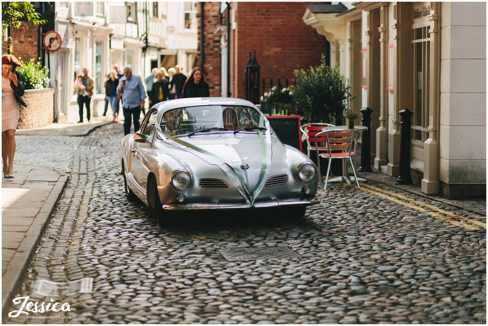 classic car delivers the bride to the Nantwich church