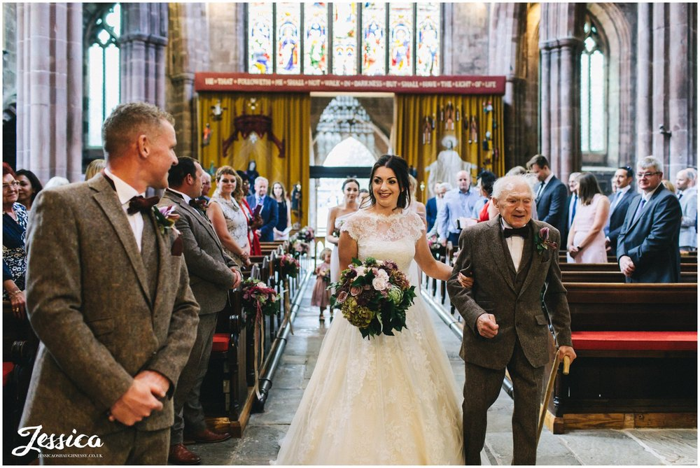 bride walks down the aisle with her grandfather