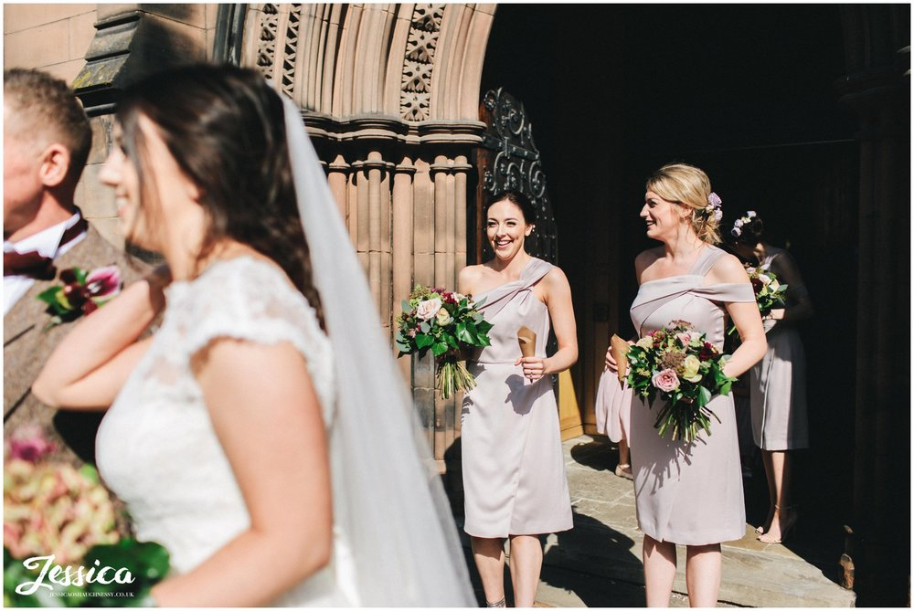 bridesmaids wait to throw confetti over the happy couple