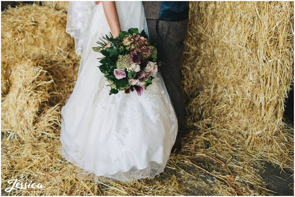bride holds her flowers next to the hay bales