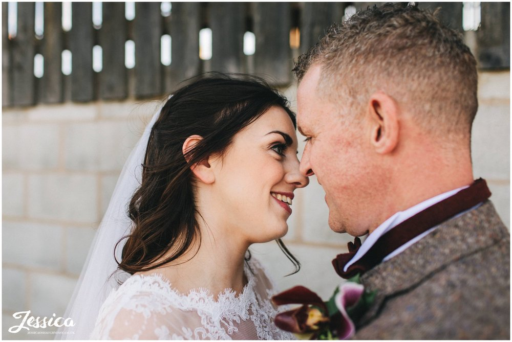 couple kiss in the farm in cheshire on their wedding day
