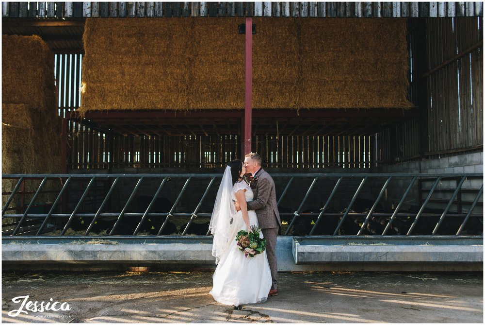 husband and wife kiss at their diy farm wedding in cheshire