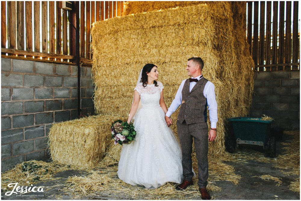 newly wed's hold hands in front of hay bales