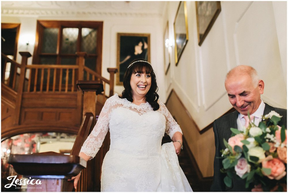 the bride walks down the stairs with her father