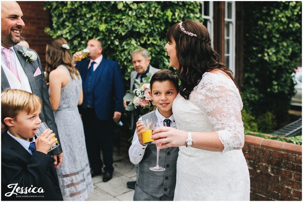 the bride hugs a child at her nunsmere hall wedding