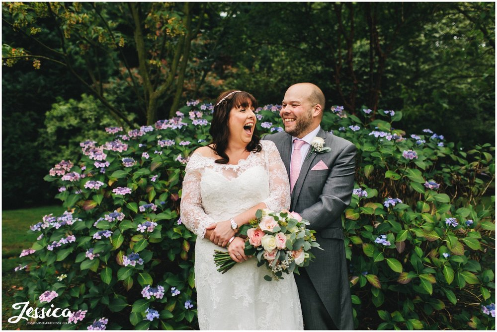 the couple laughing together in front of the flowers