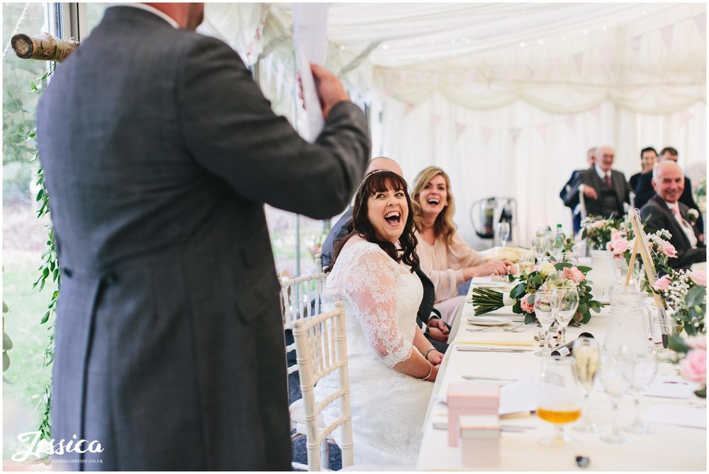 the bride laughs as the best man gives his speech