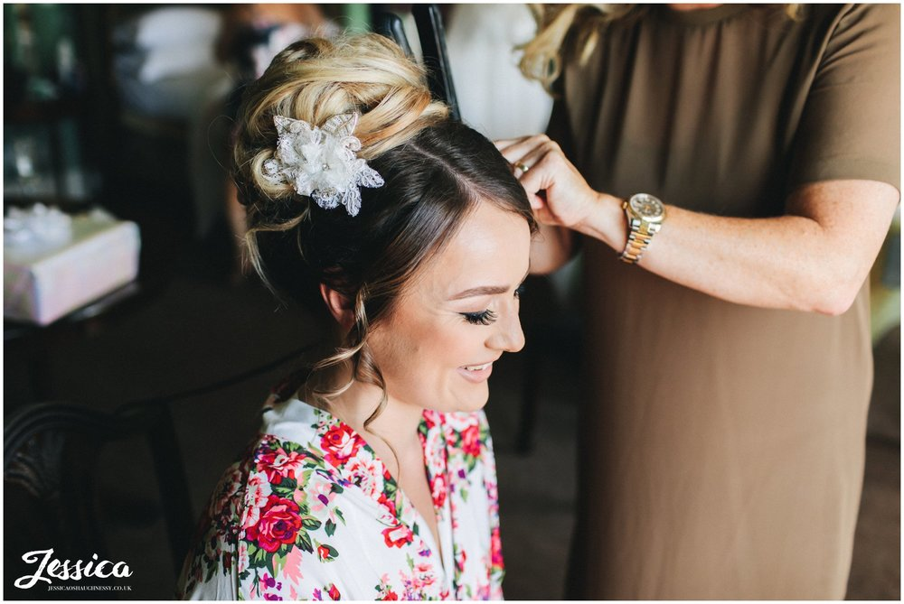 the bride has her hair done on the morning of her wedding