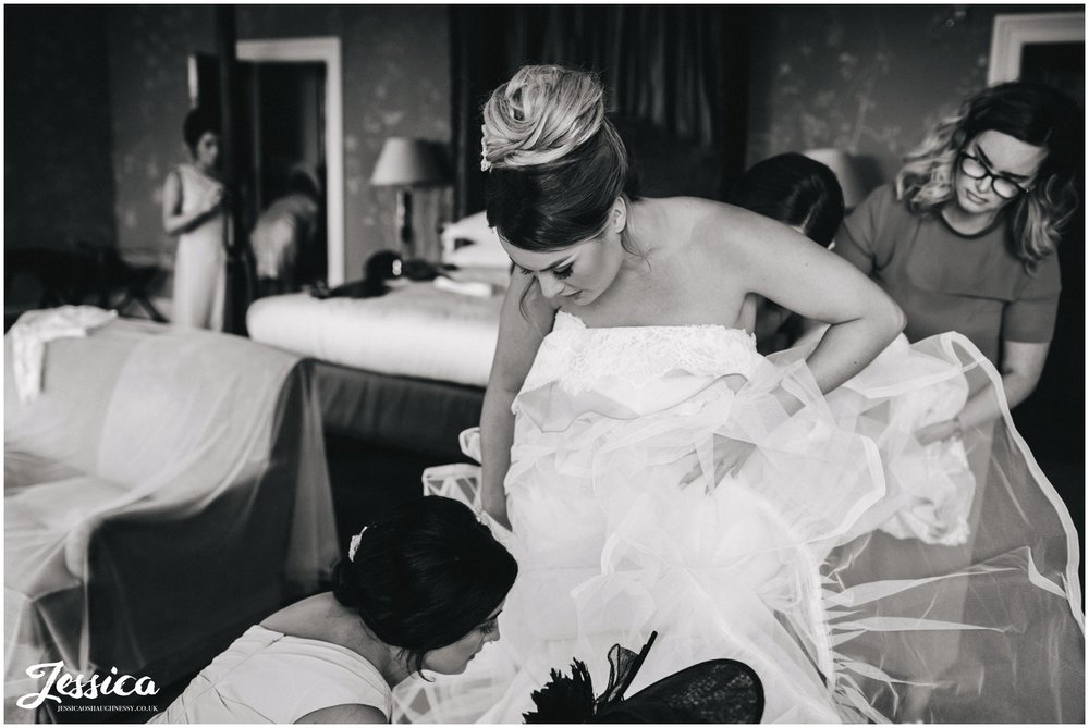 everyone helps the bride into her wedding dress at stubton hall, newark
