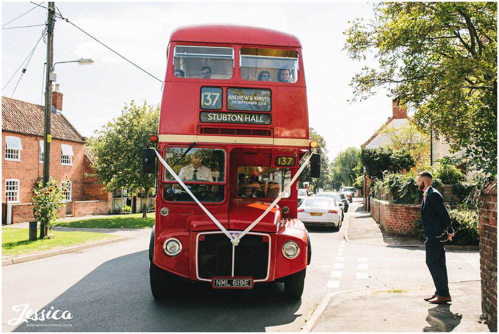 big red bus delivers the wedding guests at the church