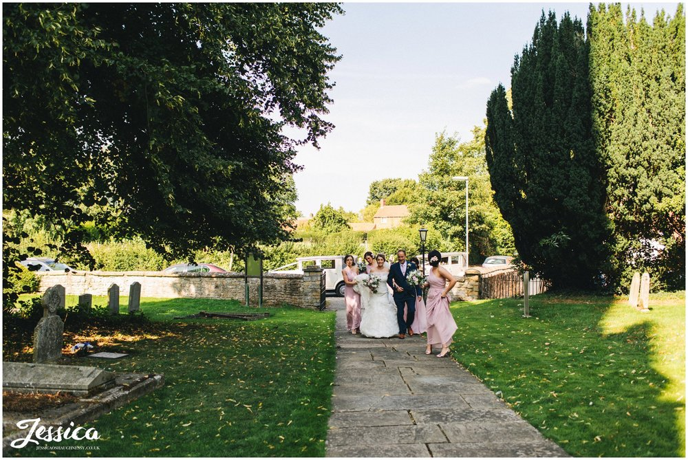 the bride walks up the church path