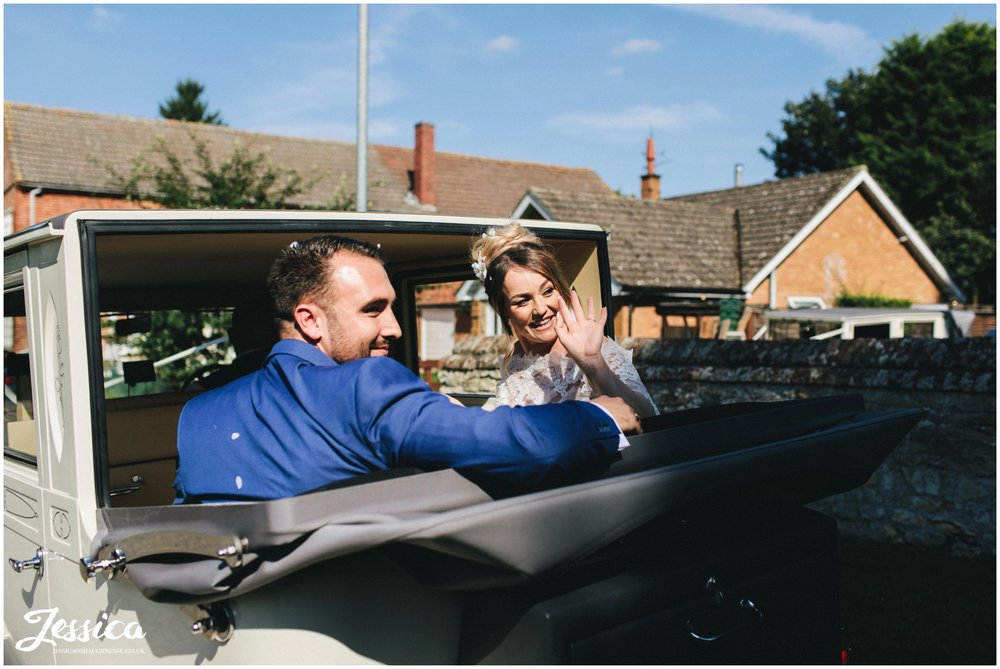 the bride & groom wave to guests as they drive off to stubton hall