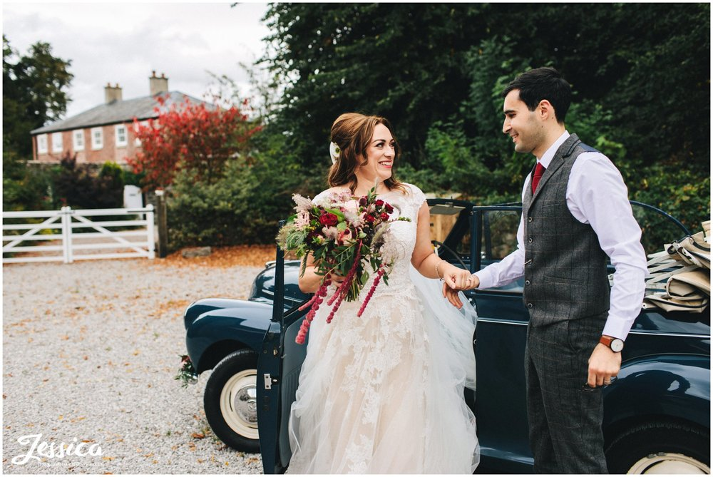 groom helps his bride out of the vintage wedding car