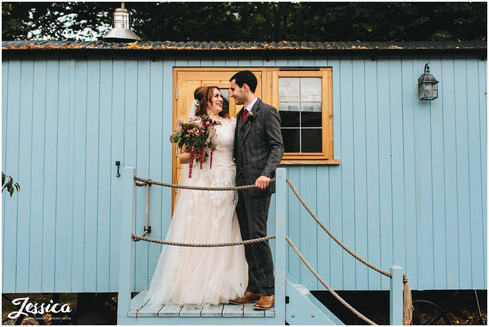couple kiss on the steps up to the shepherds huts