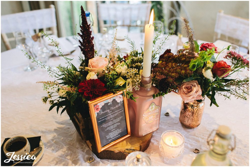 floral displays and gin bottles decorate the tables