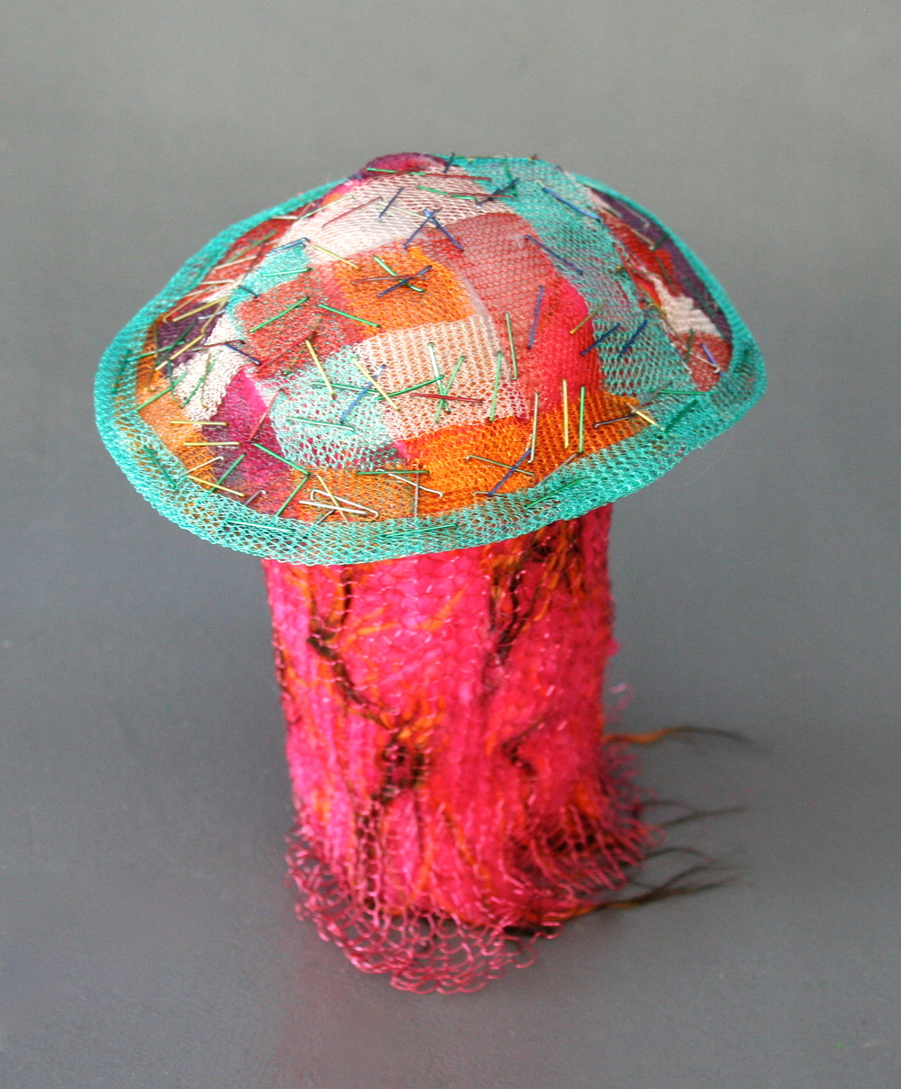 Woven ribbons of wire knit stapled together with colored staples, trimmed in wire knit, on a wire knit cage with faux fur inside