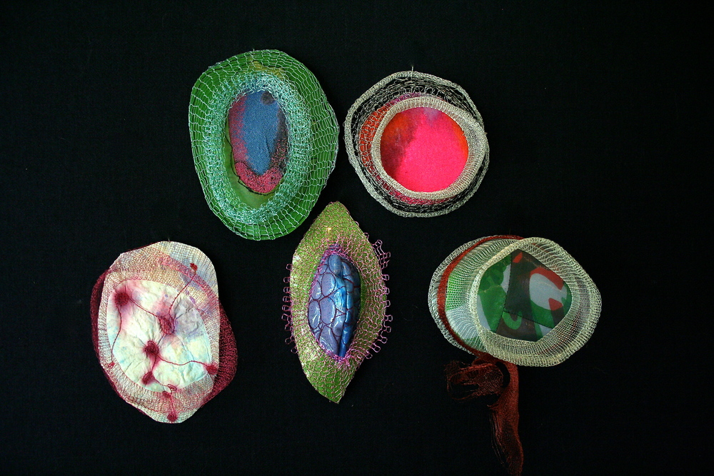 L-R, T-B: Micro beading on vinyl with wire knit; Dyed industrial felt with wire knit; dyed paper with free motion stitching and wire knit; free motion stitching on painted vinyl with wire knit; artist's screen print on fabric, quilted, in wire knit cage