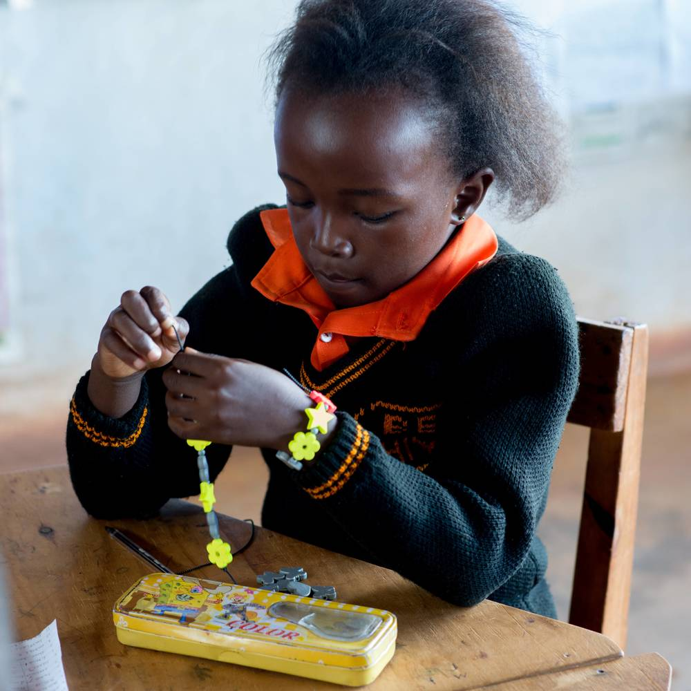 Children at BeeHive School, Malawi making reflective bracelets.