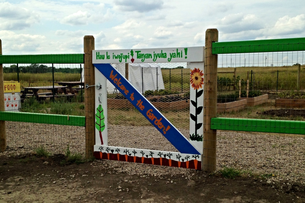 "We're glad you've arrived!:  The La Plant community garden garden gate displays both the masculine and feminine Lakota phrases for ""welcome."" By providing both the feminine and masculine terms, one elder suggests it brings balance and protection to the growing space. (A.Gross, July 2014)"
