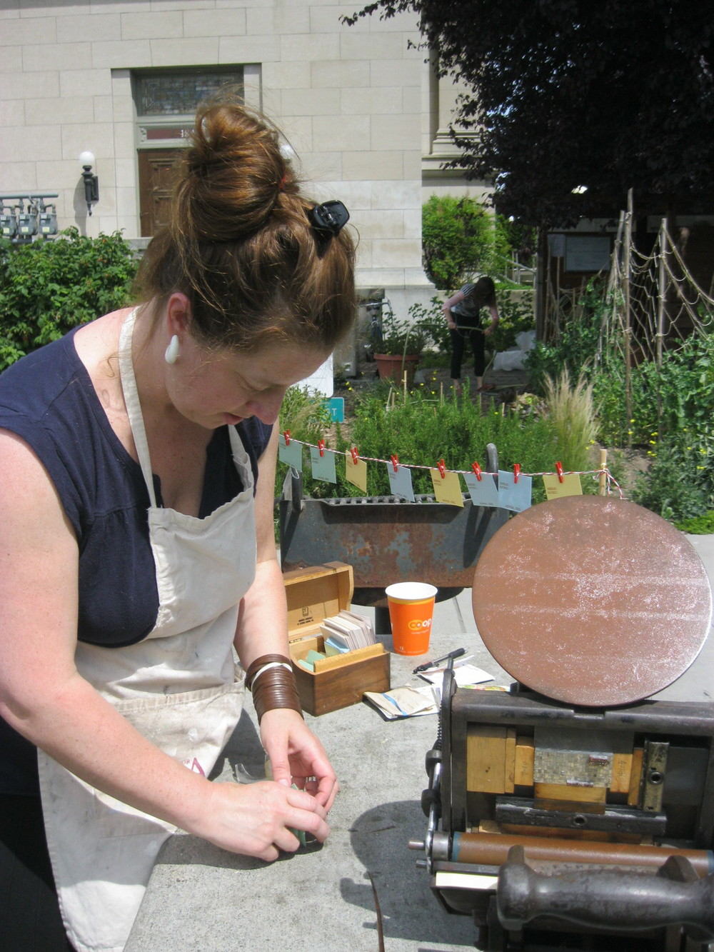 Lark prepares the portable letterpress to imprint seed packets. Gardeners pressed their own seed envelopes to take home.
